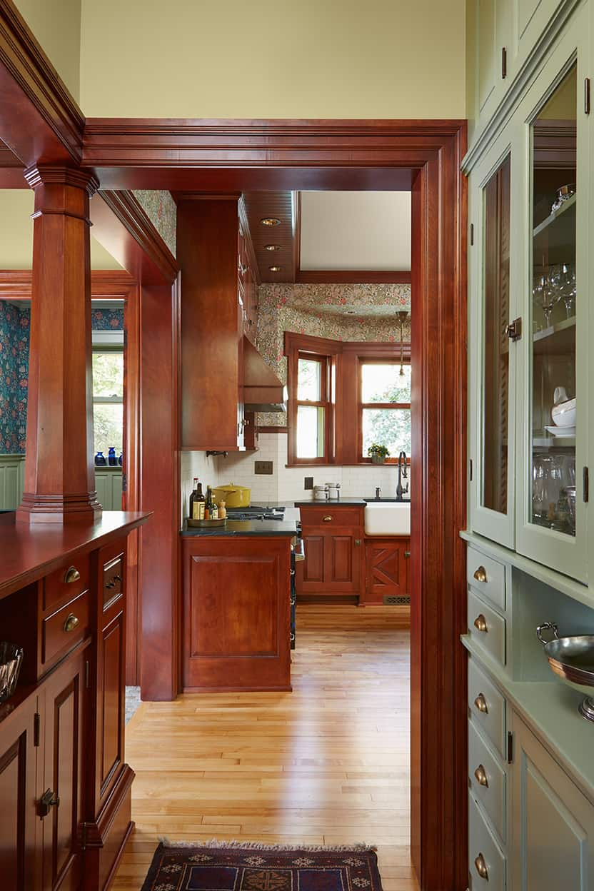 The view from the butler's pantry into the kitchen shows off the clever use of columns, half-walls, and large openings to divide an open space without closing anything off.