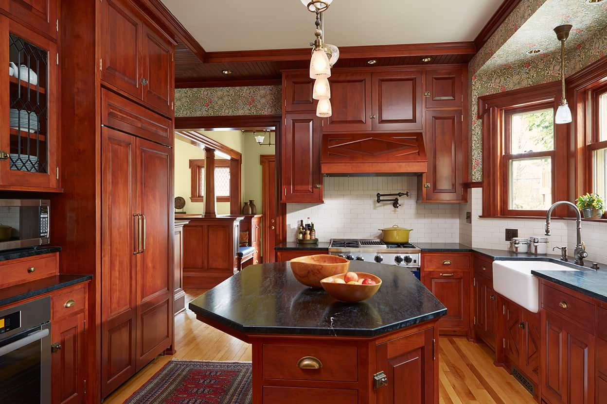 Red-toned woodwork in a darker shade in a simple yet elegant style is used throughout the first floor, including the kitchen, where it's accented by copper hardware. The wood is broken up by black stone counters, cream subway tile backsplash, and a honey-toned hardwood floor. There's a large oblong octagonal island and a farmhouse sink.