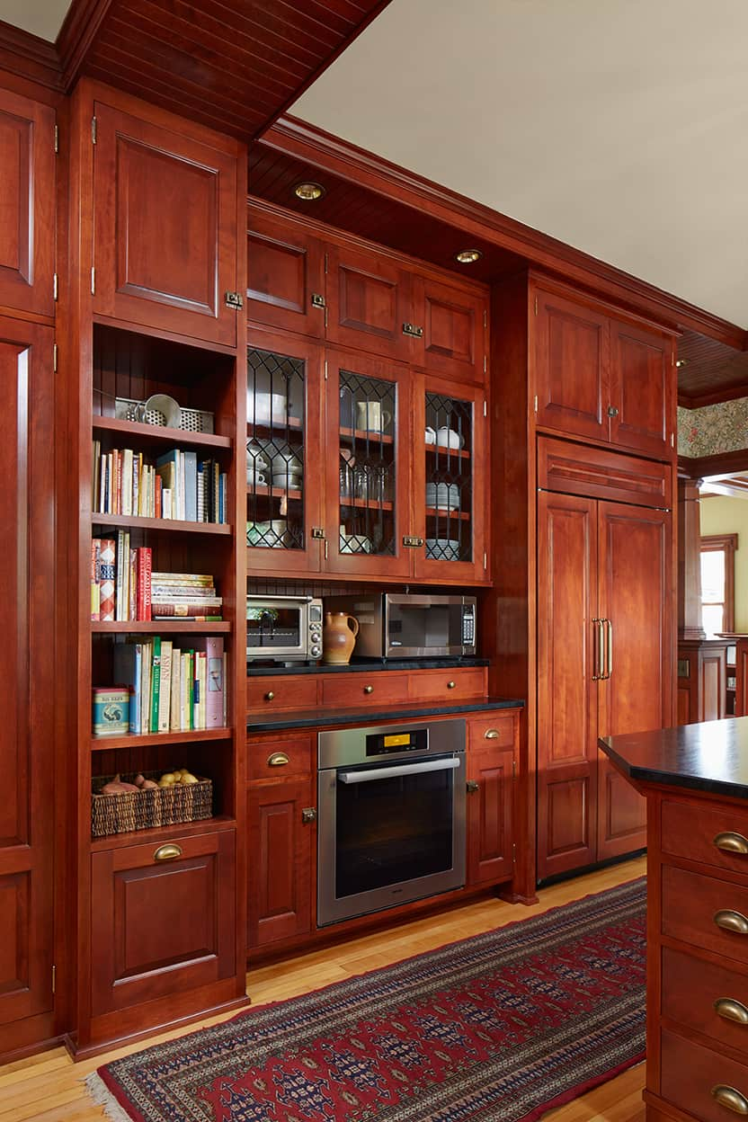 The kitchen's storage wall features open shelves for cookbooks, cabinets with leaded glass for display, a place for smaller appliances, and a fridge hidden behind matching cabinet panels.