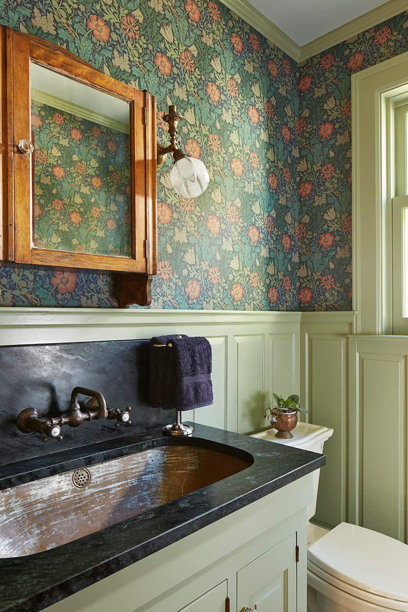 The powder room matches the mudroom. The vanity top matches the kitchen, and the sink is metal, oval, and underhung.