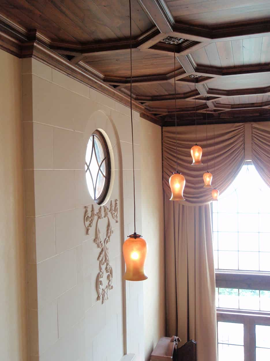 Detail view of the living room ceiling featuring the hand-blown pendant light fixtures, elaborately coffered dark wood ceiling, and the acanthus leaf plaster detail below the round window.