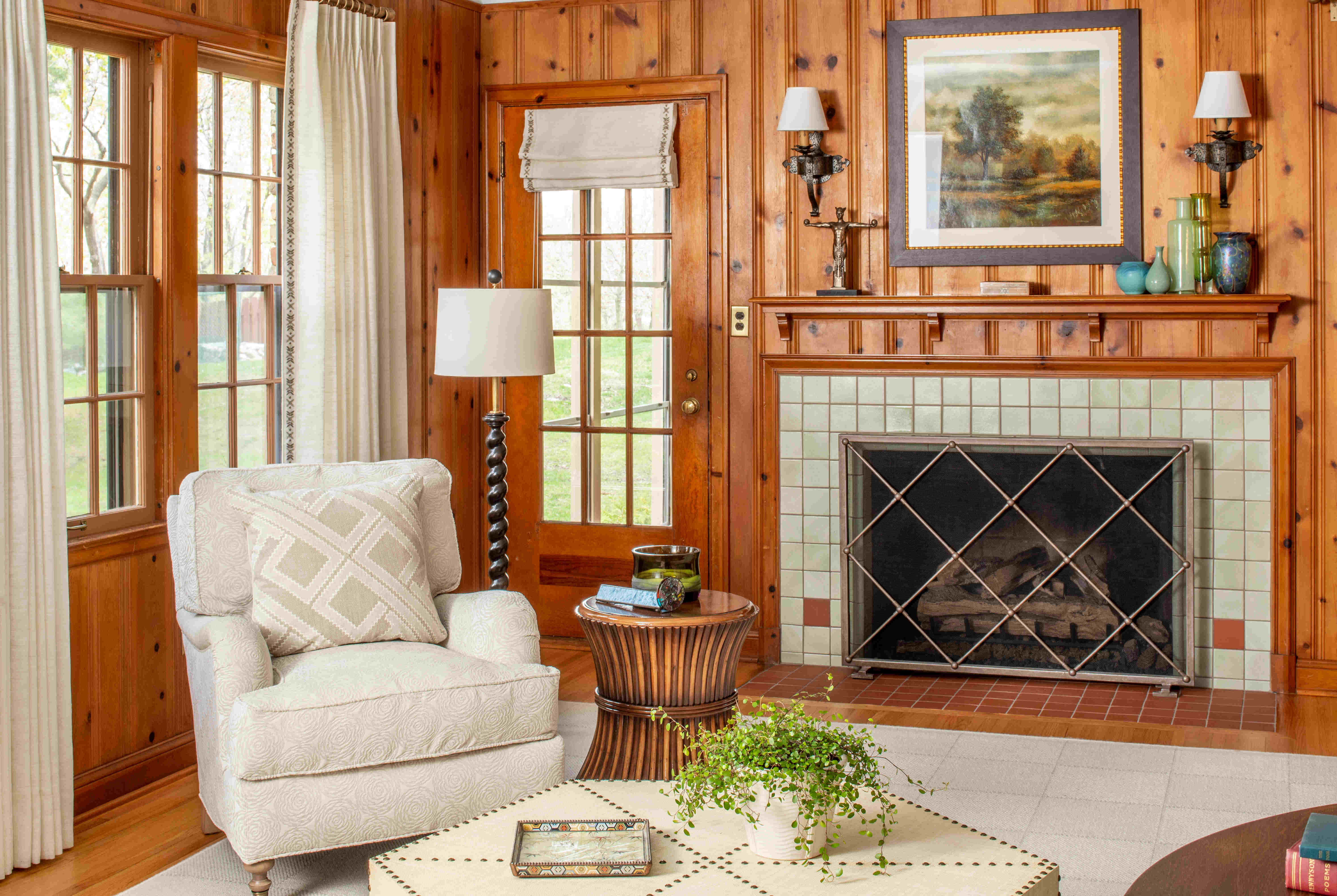 Homey wood-paneled living room with fireplace and light colored furnishings. Minnetonka Charmer.