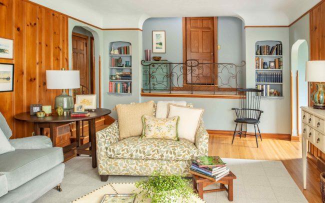 Homey living room with balcony, bookshelves, light blue walls, and light colored furnishings. Minnetonka Charmer.