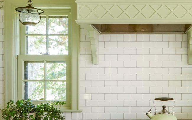 Cozy light-green kitchen details - stainless steel stove, painted wood range hood, and white subway tile backsplash. Minnetonka Charmer.