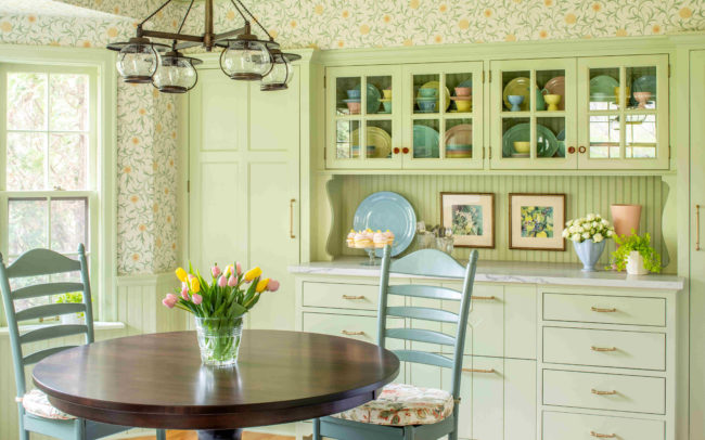 Cozy light-green kitchen with floral wallpaper, table, and built-in hutch. Minnetonka Charmer.