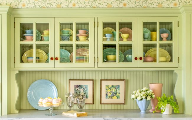 Cozy light-green kitchen detial - glass-doored hutch with pastel dishes. Minnetonka Charmer.