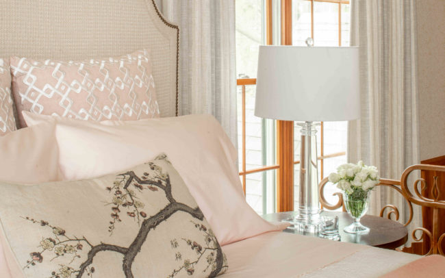 Restful elegantly neutral wallpapered bedroom with padded headboard and luxurious bedding. Minnetonka Charmer.
