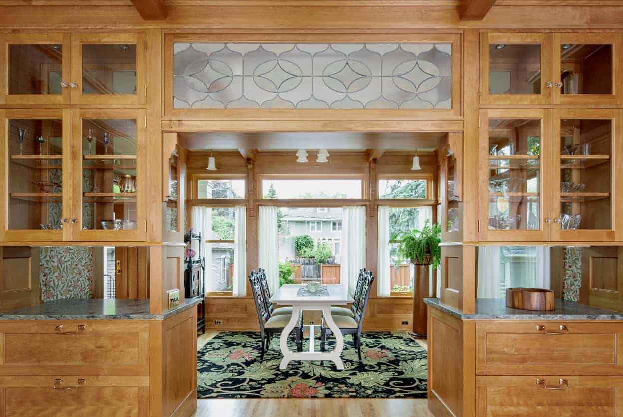 Between the kitchen and breakfast room are two towers of cabinetry, one on each wall - the uppers framed in wood but glassed in on all sides over pass throughs and then, on the bottom, capacious drawers. Connecting them is a decorative art glass transom, the final element creating a wide opening.