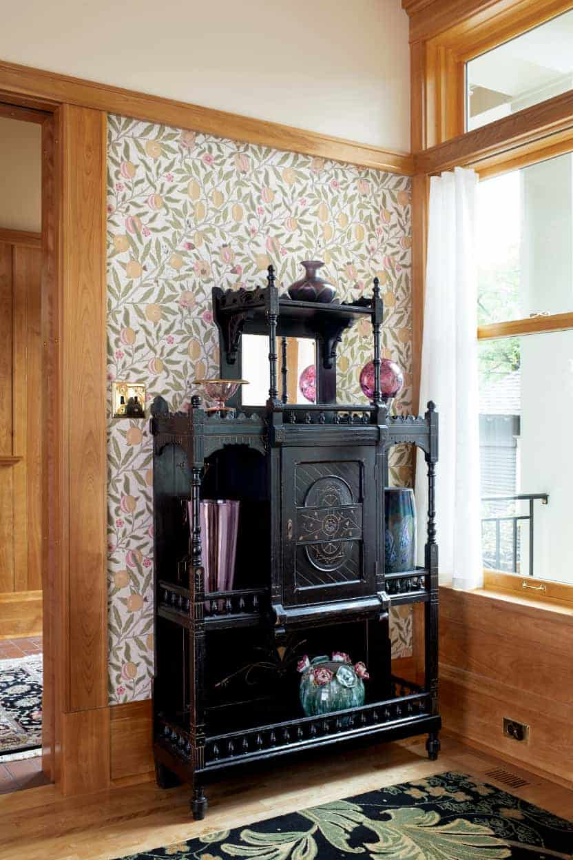 A black, highly ornamented Victorian cabinet graces the breakfast room, displaying colored glass objet d'art.