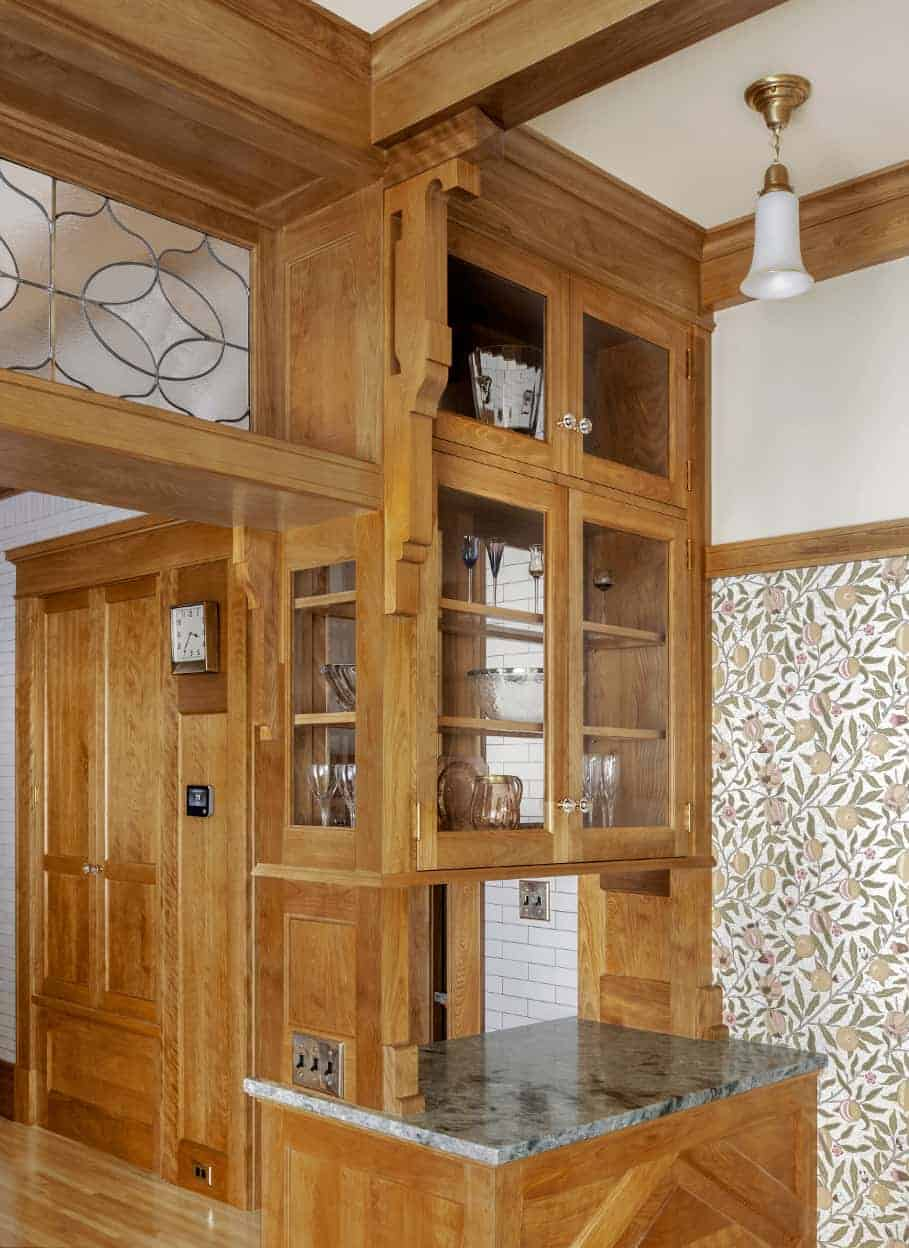 Detail of the see-through cabinetry, and the muted green and peach botanical wallpaper in the dining room.