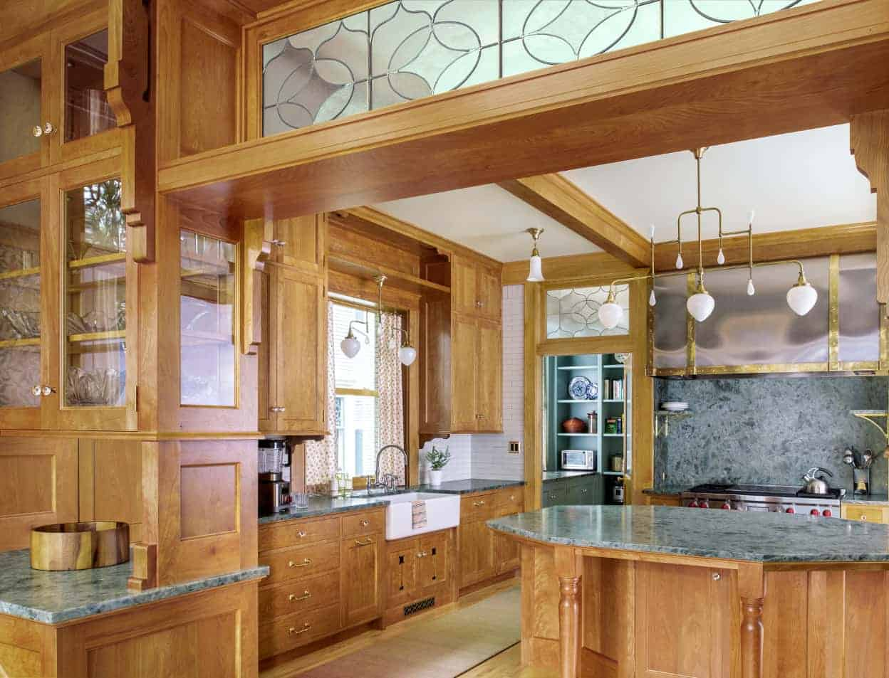 Brushed brass tubular chandeliers with white teardrop shades hang over the island and farmhouse sink, supplementing the large window over the sink. There's also a glimpse of the blue-green pantry, which harmonizes beautifully with the counters.
