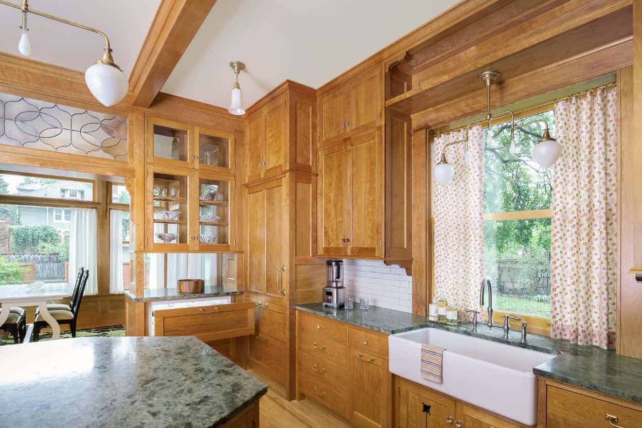 An additional refrigerator drawer makes for handy access to drinks, and most of the appliances are paneled to hide among the rest of the cabinetry. Additional pendant lights supplement the two chandeliers.