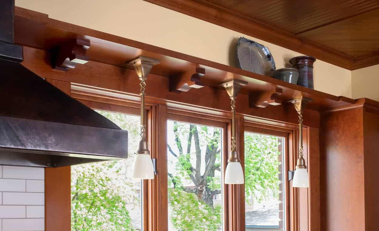 The graceful, artisan-made pendant light fixtures hang from a display shelf running around the room at top-of-cabinet height.