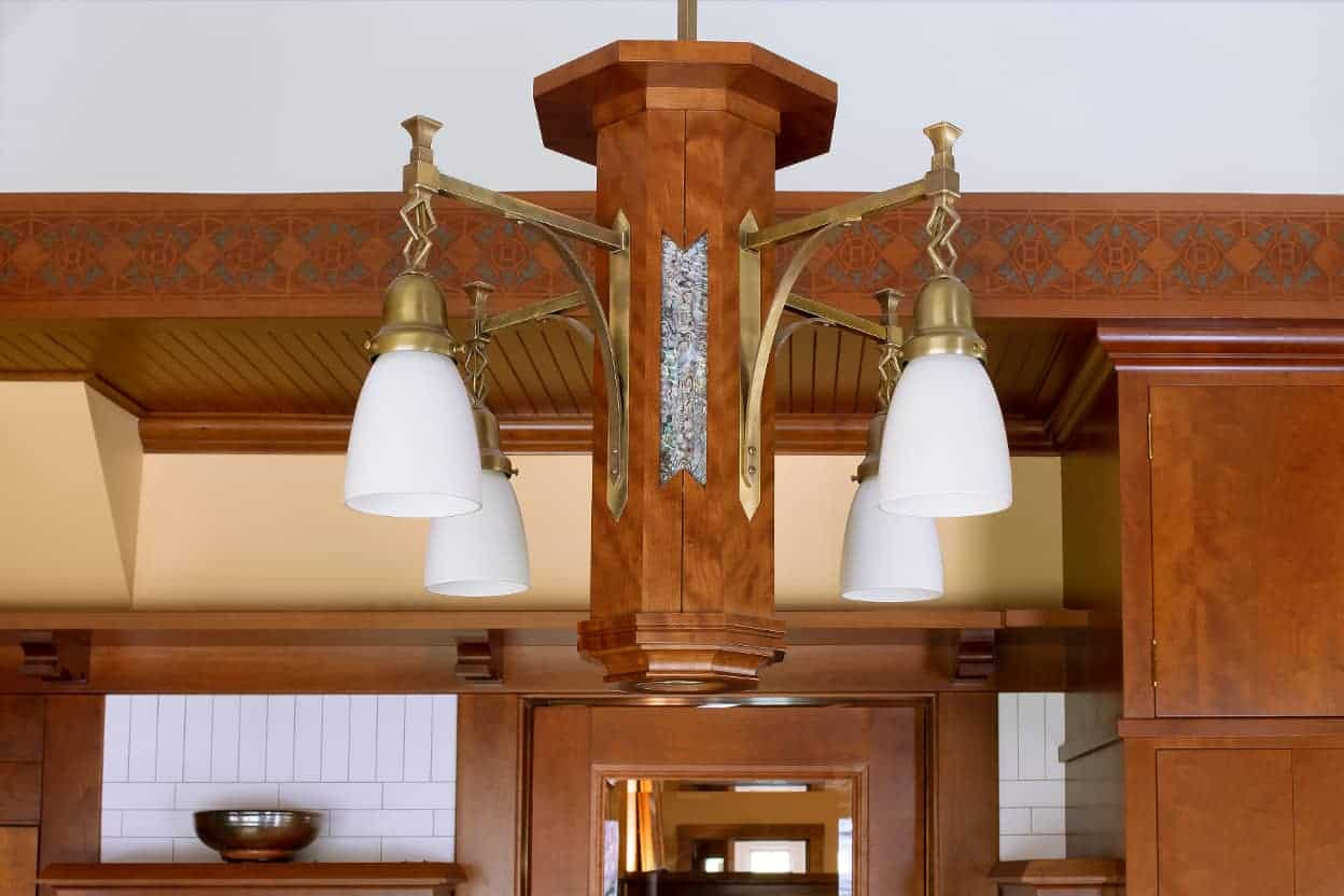 The matching chandelier includes mother of pearl detail and harmonizes with the delicate stenciling that runs around the kitchen on the wooden edge below the tent ceiling.