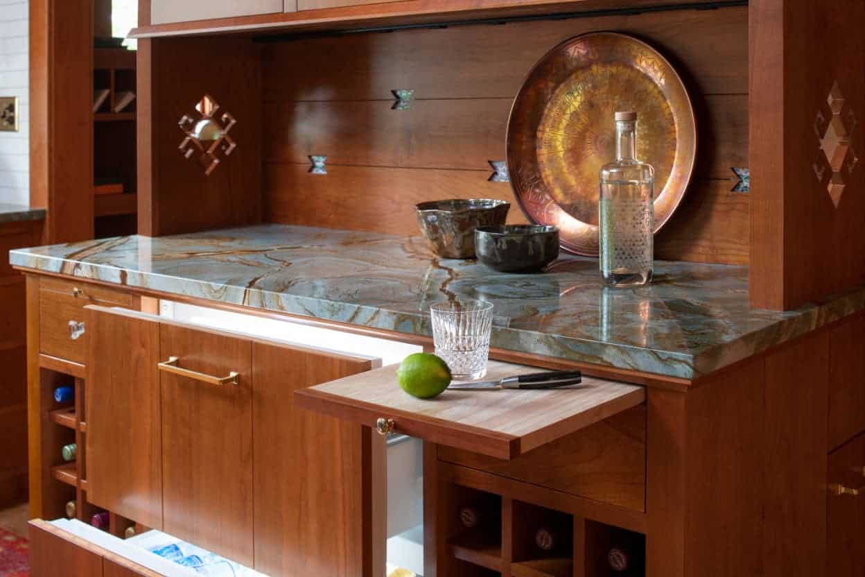 The built-in buffet with it's decorative cut-outs acts as a bar, with storage for bottles, refrigerator drawers, and pull-out cutting boards.