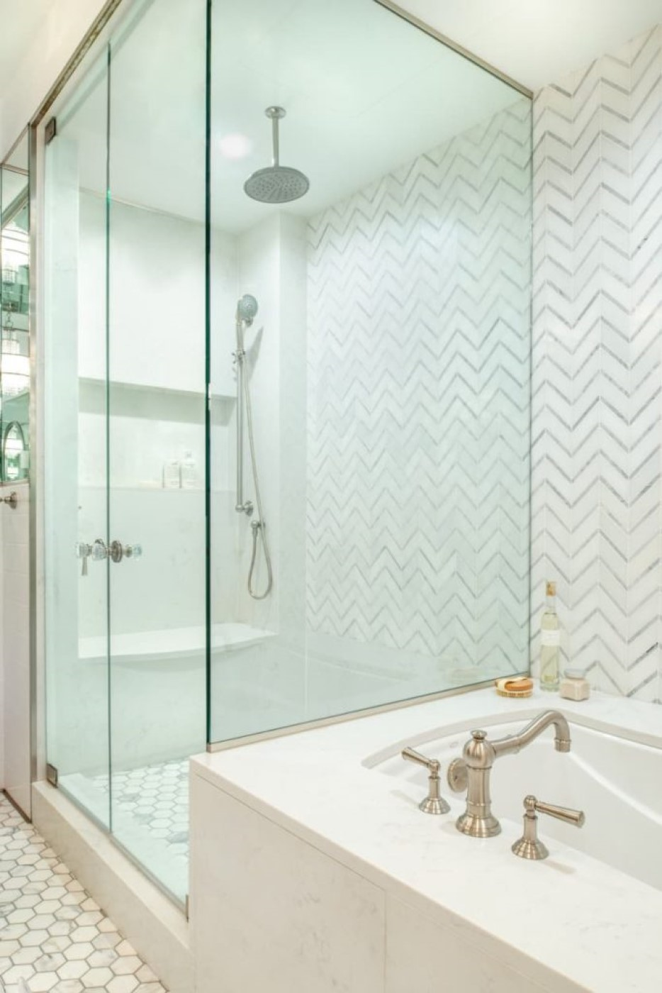 The glass shower is generously sized, with a bench seat, a large nook for bottles, and both rain and hand-held shower heads.