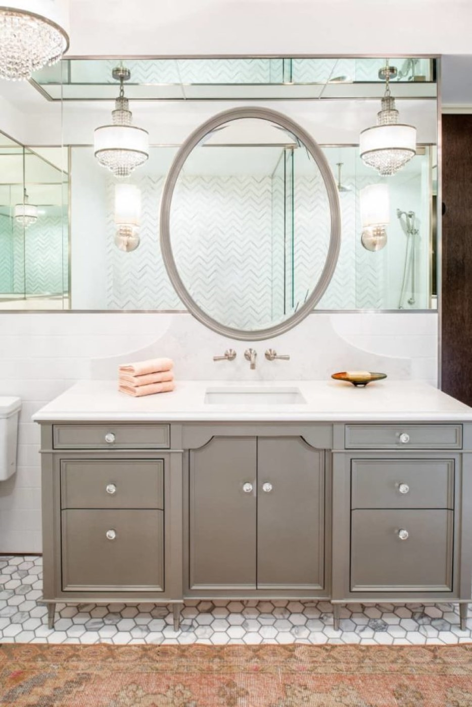 Start with an elegantly simple gray vanity with a white quartz counter atop a gray and white marble hex tiled floor. Add a gray-framed oval mirror mounted on a tall strip of mirrors framed by white stone, all under a mirrored ceiling. Finish off with crystal chandeliers. The result is a dazzling symphony of gray, white, and glass.