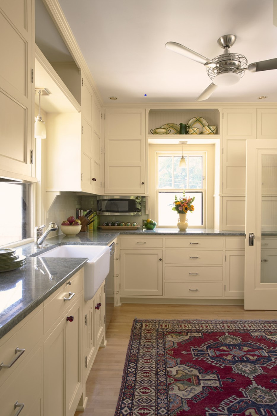 Kitchen showing ceiling fan, cream cabinetry and woodwork, gray stone counters, and hardwood floor