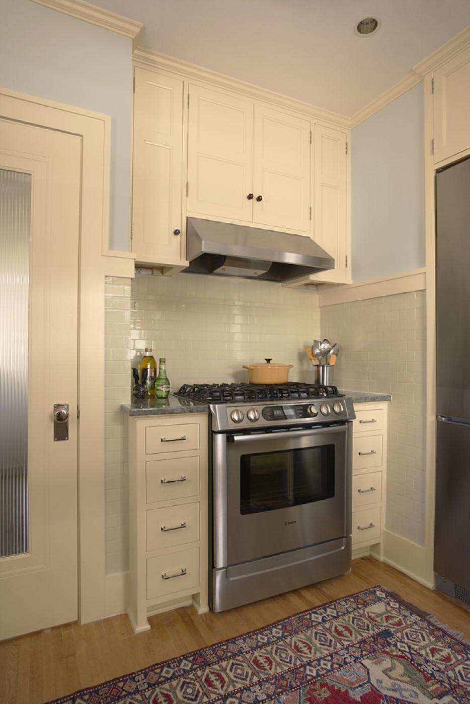 Kitchen stainless steel stove and very light gray tile backsplash